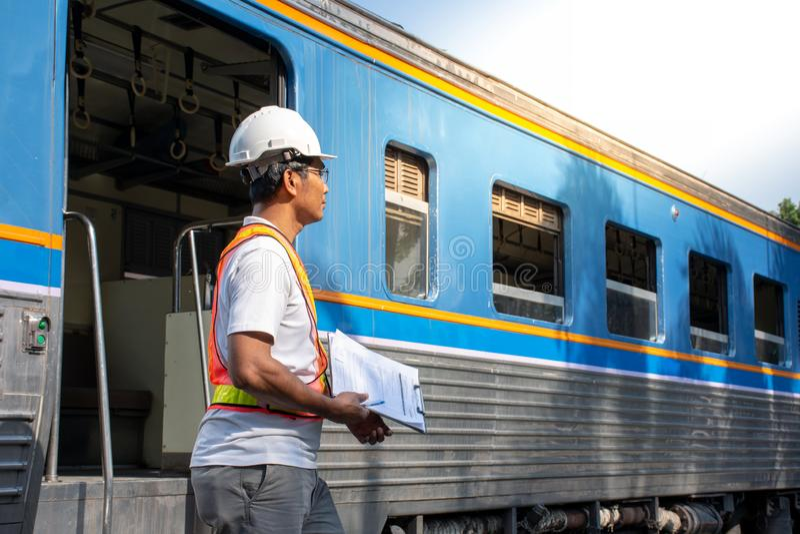 Ασιατικός μηχανικός που φορά το κράνος ασφάλειας με τον έλεγχο του τραίνου για τη συντήρηση στην έννοια σταθμών/μηχανικών στοκ εικόνα με δικαίωμα ελεύθερης χρήσης