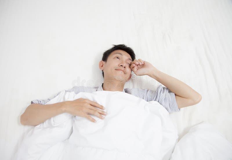 Ασιατικός νεαρός άνδρας που τεντώνει ξυπνώντας το πρωί στοκ φωτογραφίες