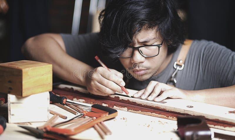 Ασιατικός ξυλουργός που εργάζεται στο εργαστήριο ξυλουργικής Παραγωγή του πνεύματος γραμμών στοκ φωτογραφία με δικαίωμα ελεύθερης χρήσης