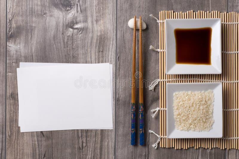 Ασιατικός πίνακας με chopsticks, τη σάλτσα σόγιας και το ρύζι και την άσπρη σημείωση στοκ φωτογραφία με δικαίωμα ελεύθερης χρήσης
