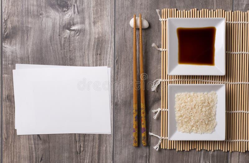 Ασιατικός πίνακας με chopsticks, τη σάλτσα σόγιας και το ρύζι και την άσπρη σημείωση στοκ εικόνα
