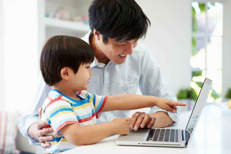 Ασιατικός πατέρας που βοηθά το γιο για να χρησιμοποιήσει το lap-top στο σπίτι στοκ φωτογραφίες με δικαίωμα ελεύθερης χρήσης