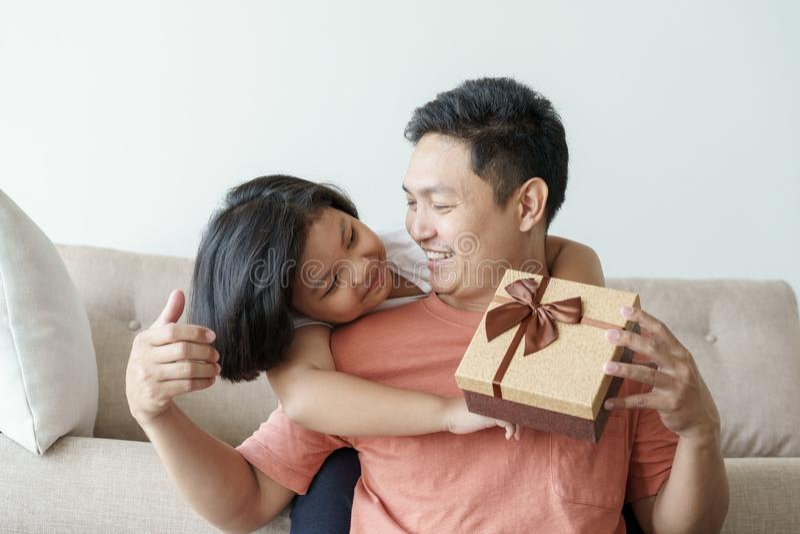 Ασιατικός πατέρας που δίνει στο κιβώτιο δώρων για την κόρη το καθιστικό Η χαριτωμένη συνεδρίαση κοριτσιών και πατέρων στον καναπέ στοκ φωτογραφία