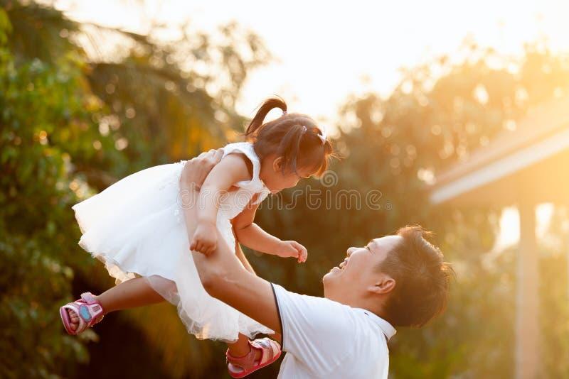 Ασιατικός πατέρας που φέρνει την κόρη του επάνω στον αέρα και που παίζει μαζί στο πάρκο στοκ φωτογραφία με δικαίωμα ελεύθερης χρήσης