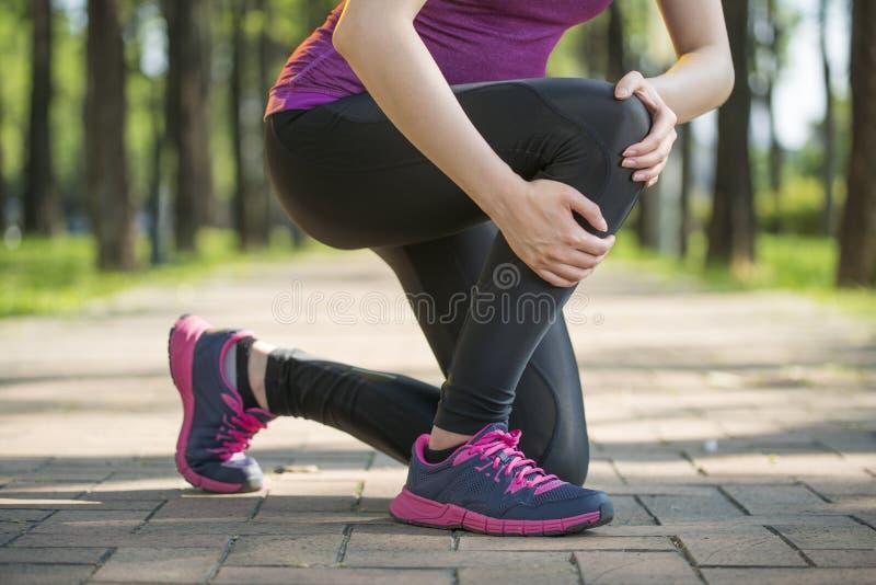 Ασιατικός πόνος γονάτων λαβής δρομέων γυναικών, ανθρώπινο πόδι στοκ φωτογραφία με δικαίωμα ελεύθερης χρήσης