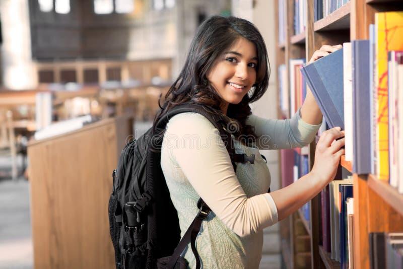 Ασιατικός σπουδαστής στη βιβλιοθήκη στοκ φωτογραφία