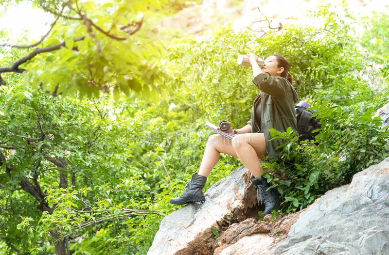 Ασιατικός ταξιδιώτης γυναικών ή πεζοπορία με συνεδρίασης ορειβασίας σακιδίων πλάτης το νερό και στα βουνά στοκ εικόνα
