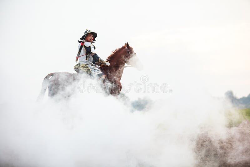 Ασιατικός ταϊλανδικός πολεμιστής στο παραδοσιακό άλογο οδήγησης κοστουμιών τεθωρακισμένων στην άσπρη ομίχλη με το αγροτικό αγροτι στοκ φωτογραφία με δικαίωμα ελεύθερης χρήσης