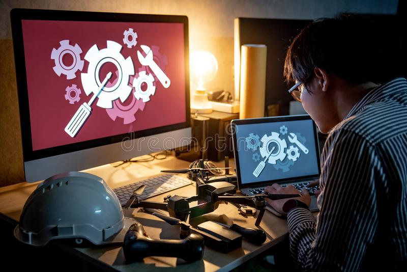 Ασιατικός τεχνικός μηχανικός που επισκευάζει τον κηφήνα χρησιμοποιώντας το lap-top στοκ φωτογραφία με δικαίωμα ελεύθερης χρήσης