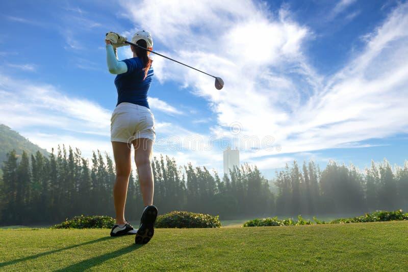 Ασιατικός φορέας γκολφ γυναικών που κάνει το γράμμα Τ ταλάντευσης γκολφ μακριά στον πράσινο χρόνο βραδιού στο υπόβαθρο μπλε ουραν στοκ φωτογραφία με δικαίωμα ελεύθερης χρήσης