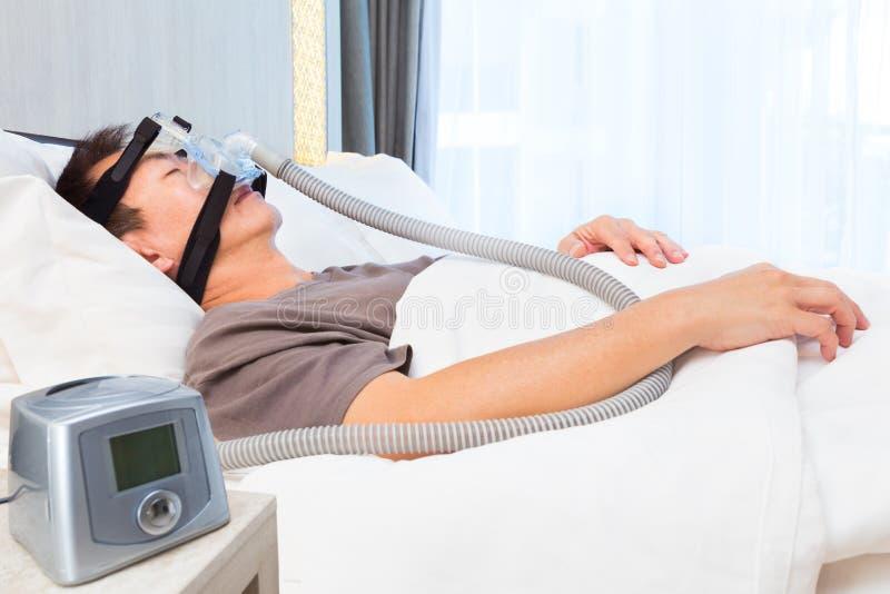 Ασιατικός ύπνος ατόμων Μεσαίωνα που φορά τη μάσκα CPAP που συνδέει με το AI στοκ φωτογραφία με δικαίωμα ελεύθερης χρήσης
