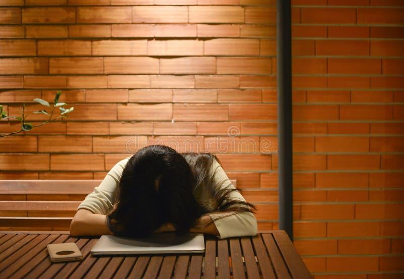 Ασιατικός ύπνος γυναικών στον πίνακα, ανεξάρτητη εργασία αργά στοκ φωτογραφίες