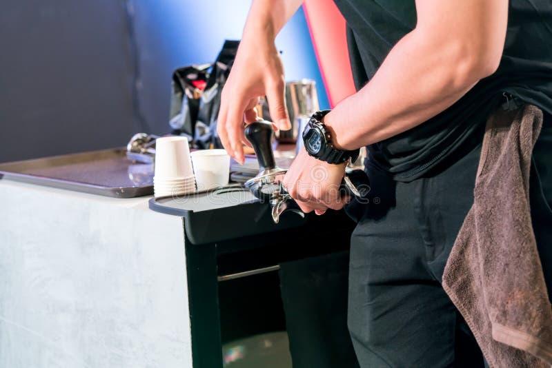 Ασιατικός tamping barista επίγειος καφές στον αντίθετο φραγμό στοκ εικόνες