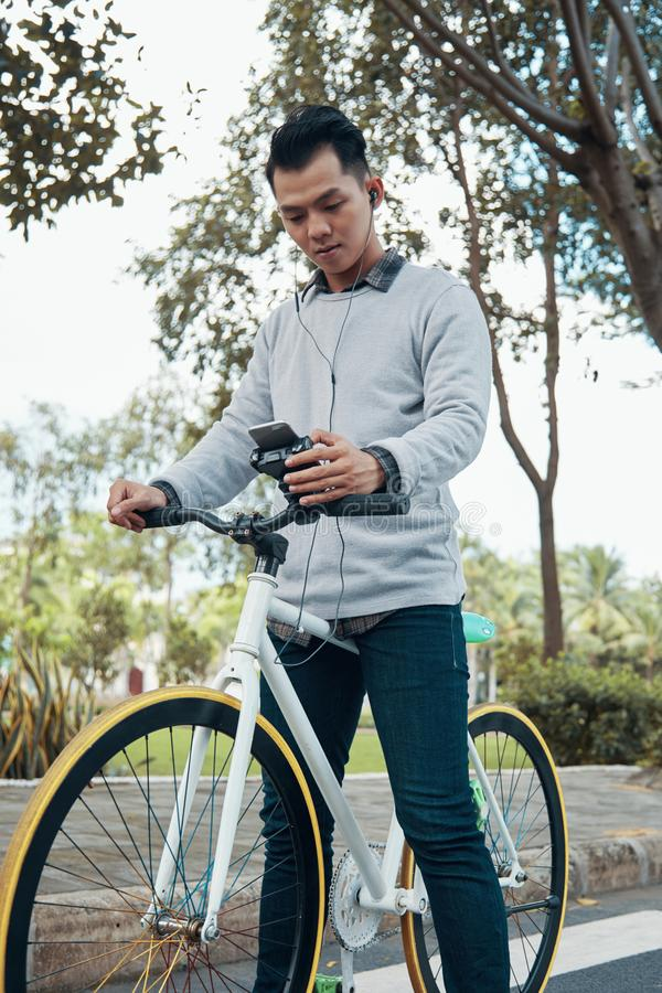 Ασιατικό άτομο με τα ακουστικά που χρησιμοποιούν το smartphone στο ποδήλατο στοκ φωτογραφίες με δικαίωμα ελεύθερης χρήσης