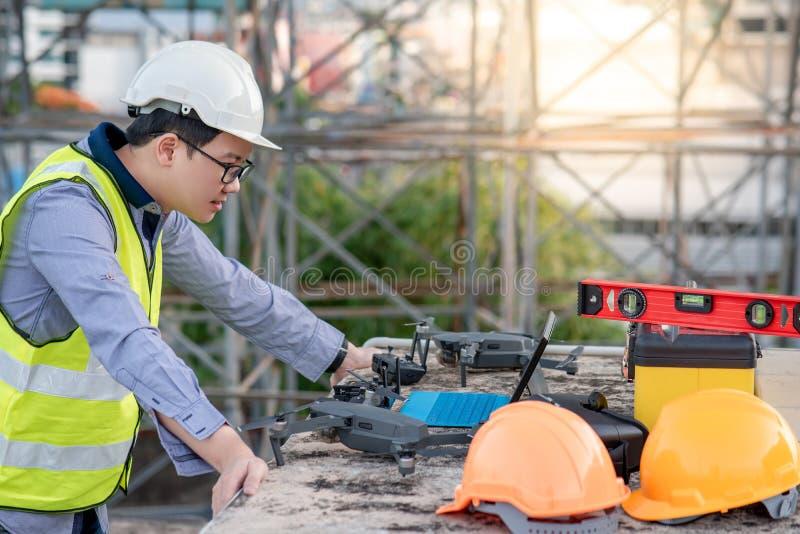 Ασιατικό άτομο μηχανικών που χρησιμοποιεί τον κηφήνα για την έρευνα περιοχών στοκ φωτογραφία