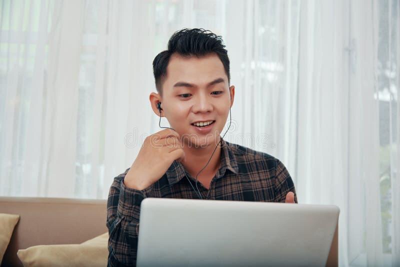 Ασιατικό άτομο που έχει την τηλεοπτική κλήση στο σπίτι στοκ εικόνες