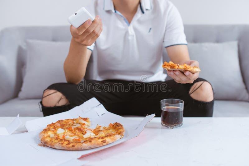 Ασιατικό άτομο που απολαμβάνει την πίτσα του καθμένος στον καναπέ που προσέχει τη TV στοκ εικόνα