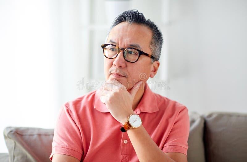 Ασιατικό άτομο που σκέφτεται στο σπίτι στοκ εικόνες