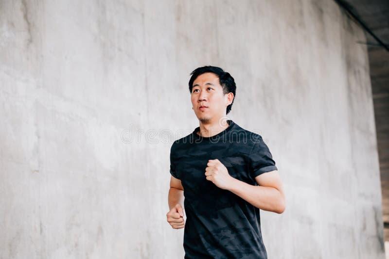Ασιατικό άτομο που τρέχει στην οδό στοκ εικόνες
