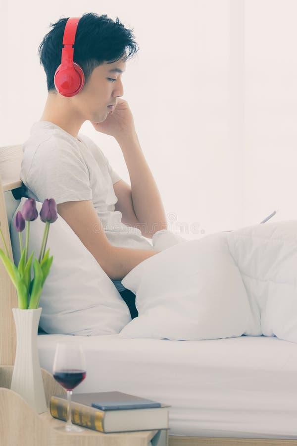 Ασιατικό άτομο που φορά το κόκκινο ακουστικό, μουσική ακούσματος στοκ εικόνα με δικαίωμα ελεύθερης χρήσης