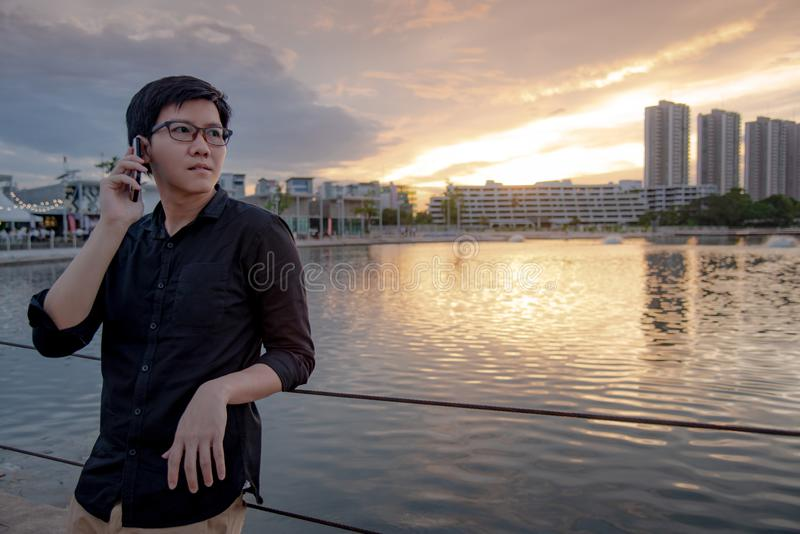 Ασιατικό άτομο που χρησιμοποιεί το smartphone στην πόλη στοκ εικόνες