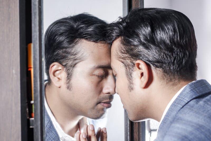 Ασιατικό άτομο στο κοστούμι που φροντίζει την εμφάνισή του μπροστά από έναν τρόπο ζωής προσδιορισμού ομορφιάς καθρεφτών στοκ φωτογραφίες