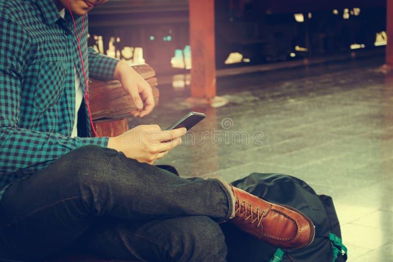 Ασιατικό άτομο hipster που κρατά το κινητό τηλέφωνο που χρησιμοποιεί app το τραγούδι με το linte στοκ φωτογραφίες με δικαίωμα ελεύθερης χρήσης