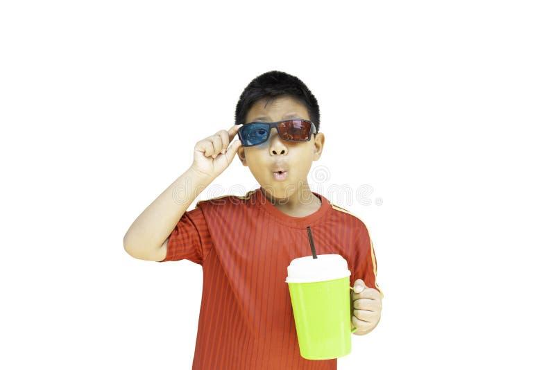 Ασιατικό αγόρι με τα τρισδιάστατα γυαλιά που κρατά την πλαστική απομόνωση φλυτζανιών στο ψαλίδισμα της πορείας στοκ εικόνες