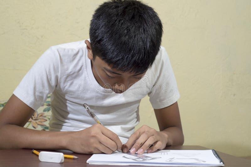 Ασιατικό αγόρι που μαθαίνει και που ασκεί για να επισύρει την προσοχή τις τρισδιάστατες μορφές στο σημειωματάριο σχεδίων στοκ φωτογραφίες