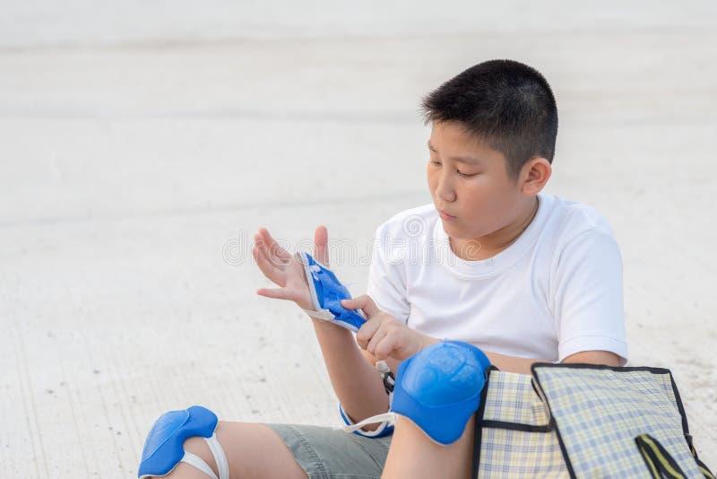 Ασιατικό αγόρι που φορά την προστασία που τίθεται για το σαλάχι στοκ εικόνα με δικαίωμα ελεύθερης χρήσης