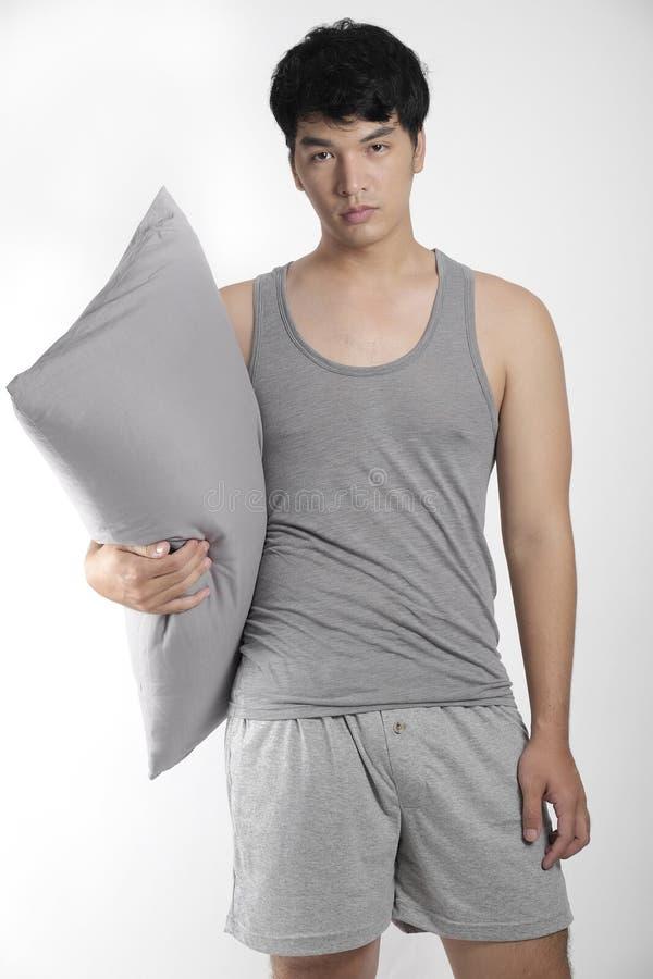 Ασιατικό αγόρι στις γκρίζες πυτζάμες με ένα μαξιλάρι στοκ εικόνες με δικαίωμα ελεύθερης χρήσης