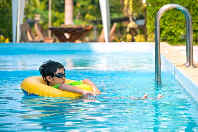 Ασιατικό αγόρι στο σωλήνα που μαθαίνει να κολυμπά στοκ εικόνα