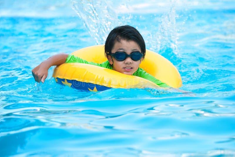 Ασιατικό αγόρι στο σωλήνα που μαθαίνει να κολυμπά στοκ φωτογραφία