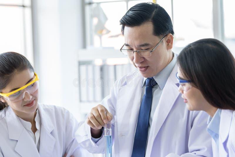 Ασιατικό ανώτερο άτομο εργαστηριακών επιστημόνων που εργάζεται στο εργαστήριο με τον ασιατικό νέο επιστήμονα σπουδαστών backgroud στοκ φωτογραφία
