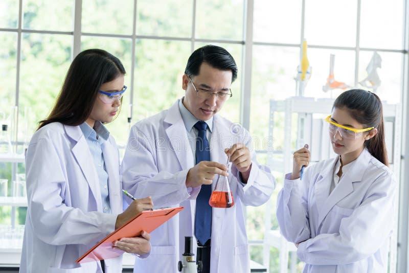 Ασιατικό ανώτερο άτομο εργαστηριακών επιστημόνων που εργάζεται στο εργαστήριο με τον ασιατικό νέο επιστήμονα σπουδαστών backgroud στοκ φωτογραφίες με δικαίωμα ελεύθερης χρήσης