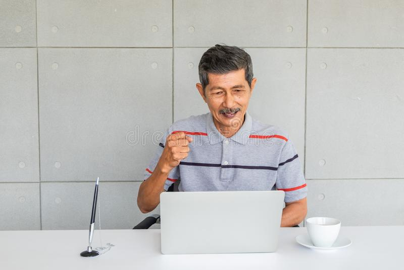 Ασιατικό ανώτερο άτομο με τα περιστασιακά ενδύματα Χαρείτε, αυξήστε την πυγμή δεξιά Το κάθισμα εξετάζει στην οθόνη φορητών προσωπ στοκ εικόνα με δικαίωμα ελεύθερης χρήσης