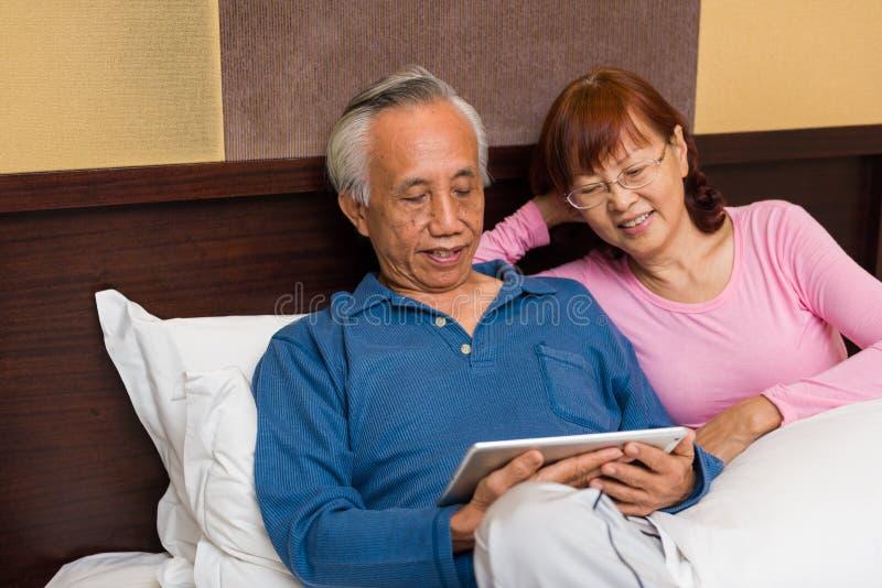 Ασιατικό ανώτερο ζεύγος που απολαμβάνει στο κρεβάτι στοκ εικόνες με δικαίωμα ελεύθερης χρήσης