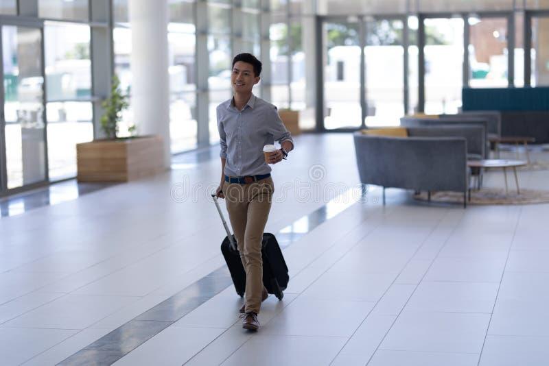 Ασιατικό αρσενικό εκτελεστικό περπάτημα με τις αποσκευές στο λόμπι στοκ εικόνες
