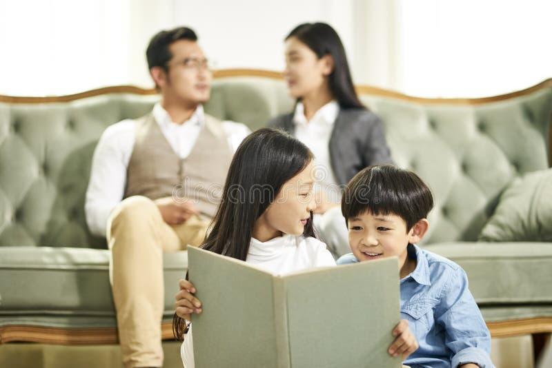 Ασιατικό βιβλίο ανάγνωσης αδελφών και αδελφών από κοινού στοκ εικόνα