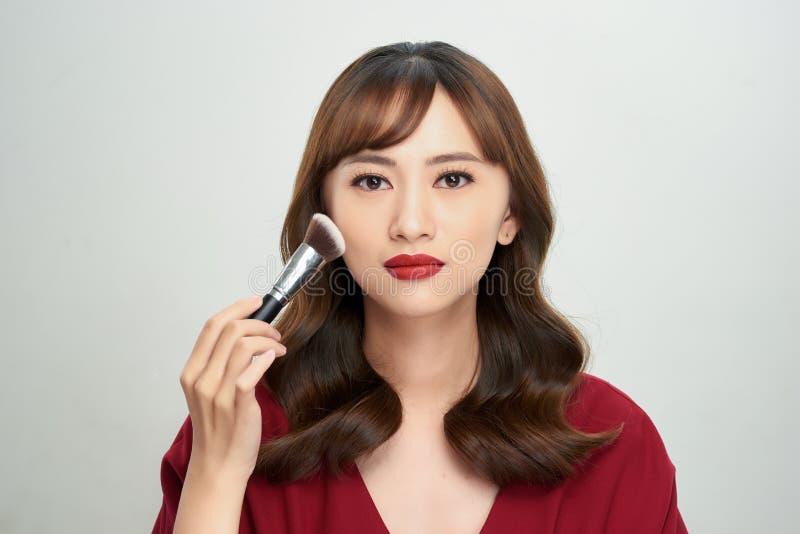 Ασιατικό δέρμα μαυρίσματος κοριτσιών ομορφιάς με τις βούρτσες Makeup Αυτή που χαμογελά και που κοιτάζει για να κονιοποιήσει τη βο στοκ εικόνες