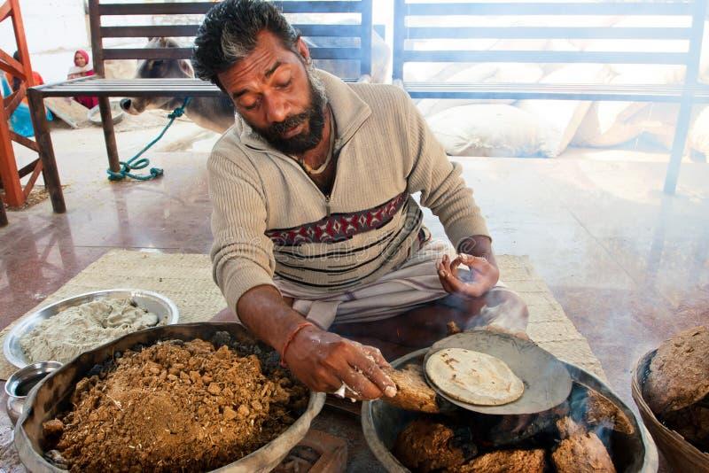 Ασιατικό εθνικό ψωμί μαγείρων ατόμων στη χαμηλή θερμότητα στοκ φωτογραφία