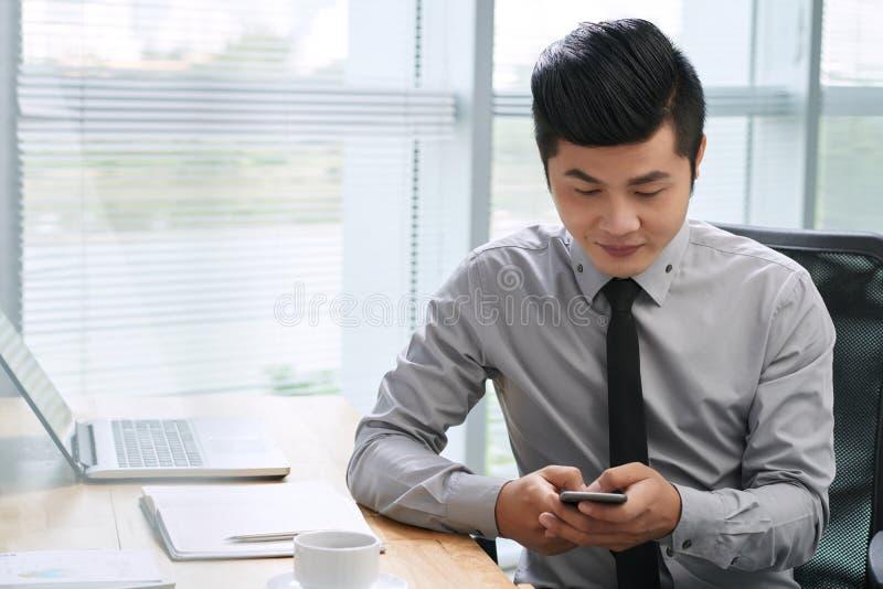Ασιατικό επιχειρηματιών στο smartphone στοκ εικόνες
