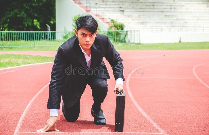 Ασιατικό επιχειρησιακό άτομο που γονατίζει στο αρχικό πλέγμα μιας τρέχοντας διαδρομής στοκ φωτογραφία με δικαίωμα ελεύθερης χρήσης