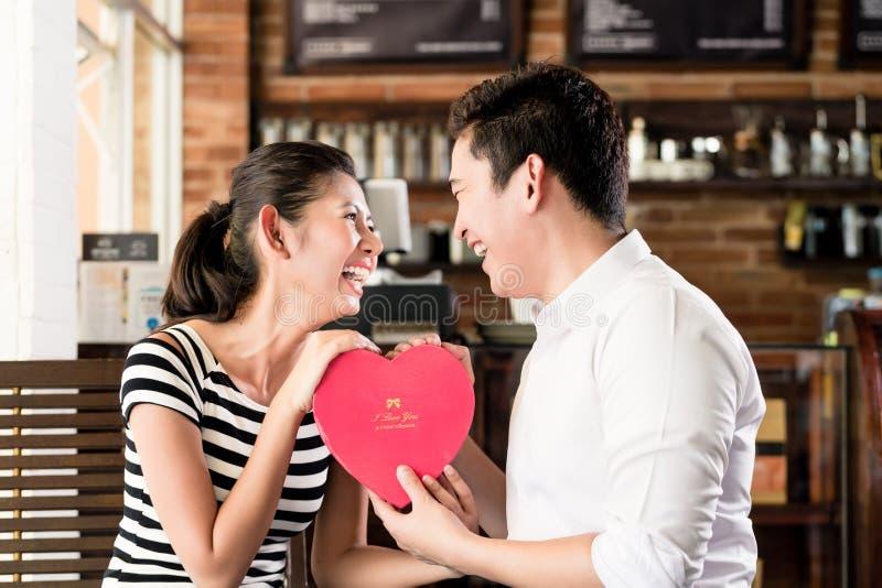 Ασιατικό ζεύγος που έχει την ημερομηνία στη καφετερία με την κόκκινη καρδιά στοκ φωτογραφίες