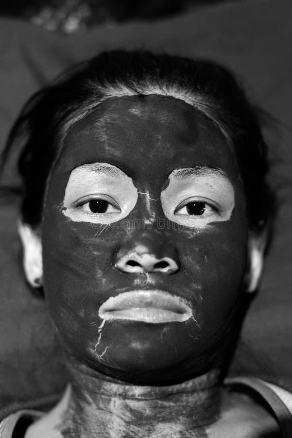 Ασιατικό θηλυκό κεφάλι με τη μάσκα λάσπης σε γραπτό στοκ φωτογραφία