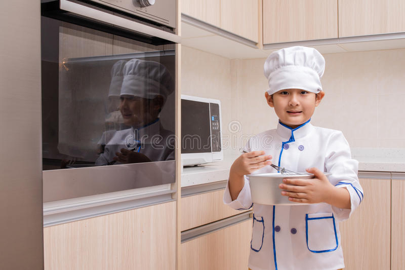 Ασιατικό κινεζικό αγόρι στα άσπρα μπισκότα ψησίματος αρχιμαγείρων ομοιόμορφα στοκ εικόνες
