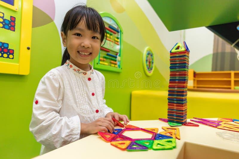 Ασιατικό κινεζικό μικρό κορίτσι που παίζει τους ζωηρόχρωμους πλαστικούς φραγμούς μαγνητών στοκ εικόνα