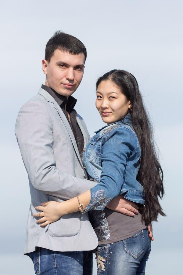 Ασιατικό κορίτσι και ευρωπαϊκή τοποθέτηση τύπων στο υπόβαθρο του ουρανού στοκ εικόνα με δικαίωμα ελεύθερης χρήσης