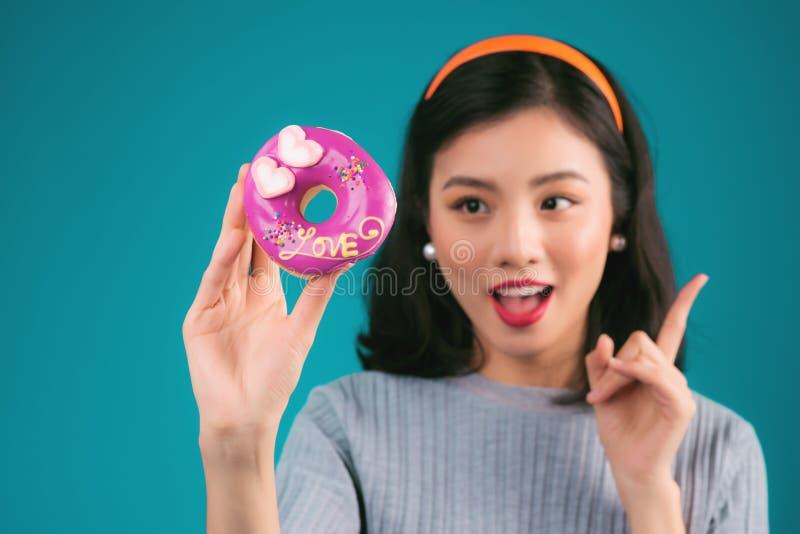 Ασιατικό κορίτσι ομορφιάς που κρατά ρόδινο doughnut Αναδρομική χαρούμενη γυναίκα με το sw στοκ φωτογραφία