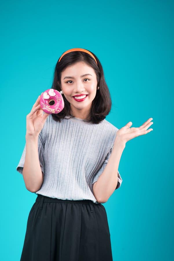 Ασιατικό κορίτσι ομορφιάς που κρατά ρόδινο doughnut Αναδρομική χαρούμενη γυναίκα με το sw στοκ εικόνα